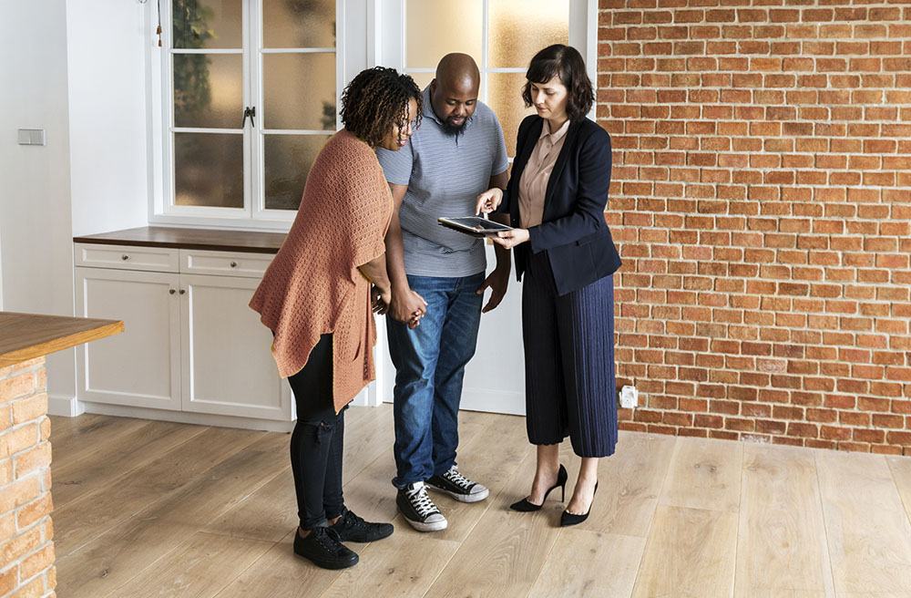 Real estate agent using a tablet to show their clients a digital home inspection report