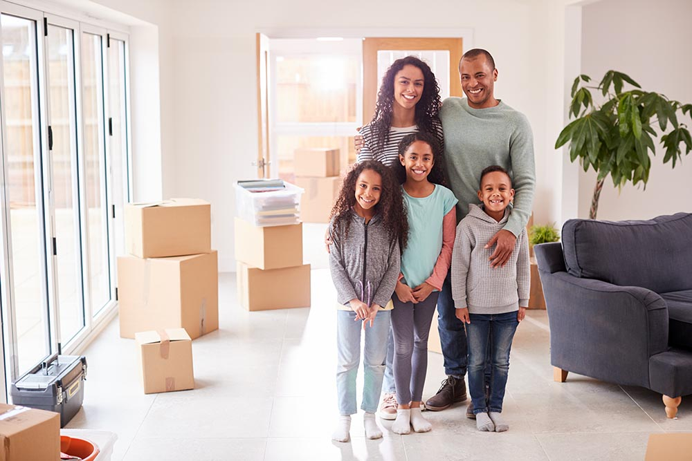 Family of four surrounded by moving boxes in their new house after a home inspection