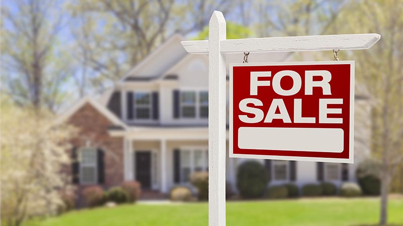 For sale sign in front of a residential real estate property before home inspection services are scheduled